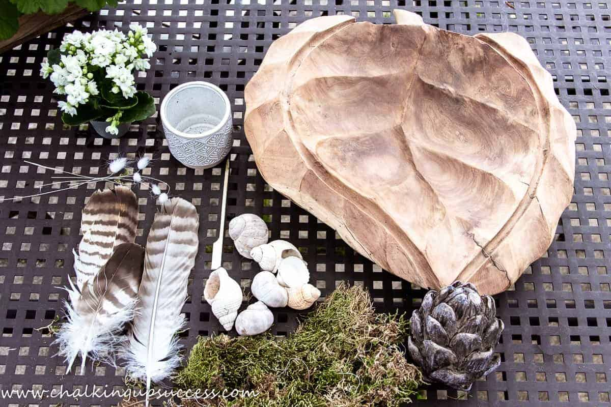 Decorate your home for summer with a wooden bowl, a small plant, a wooden artichoke, seashells, moss and feathers.