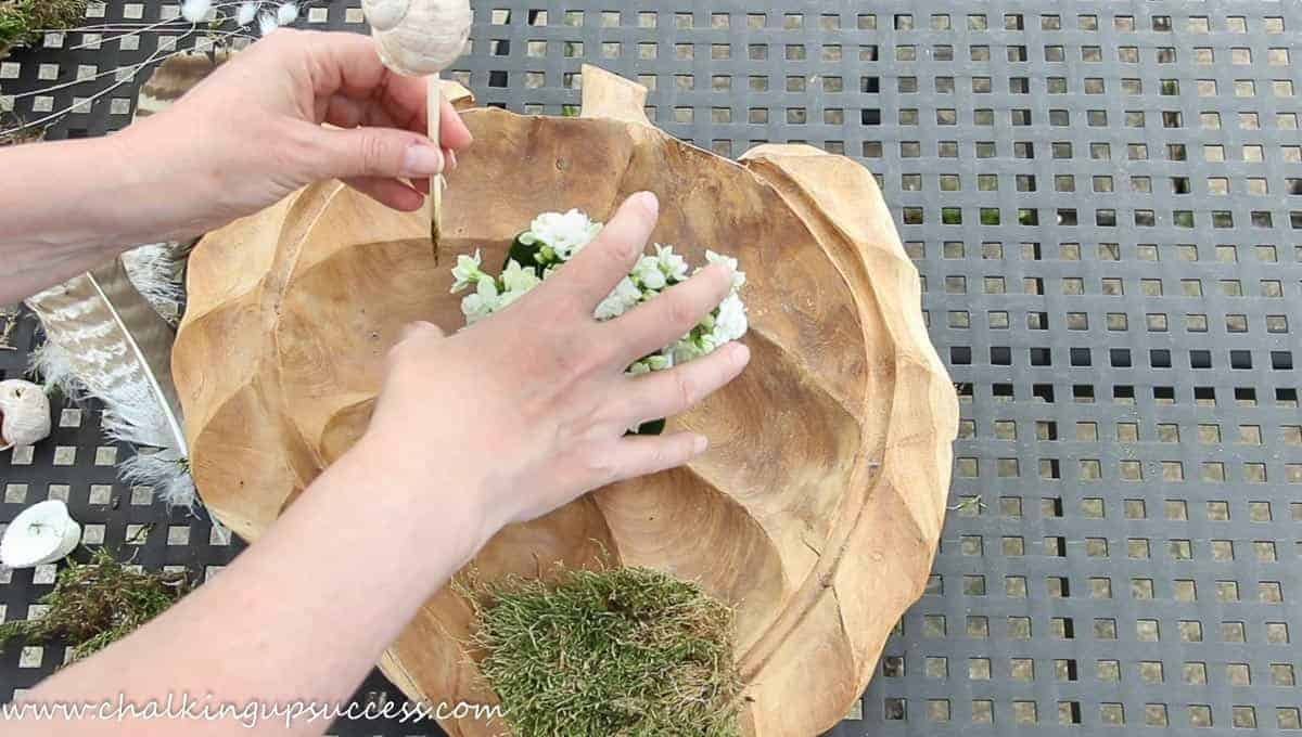 A person adding a flowering plant to a wooden bowl.