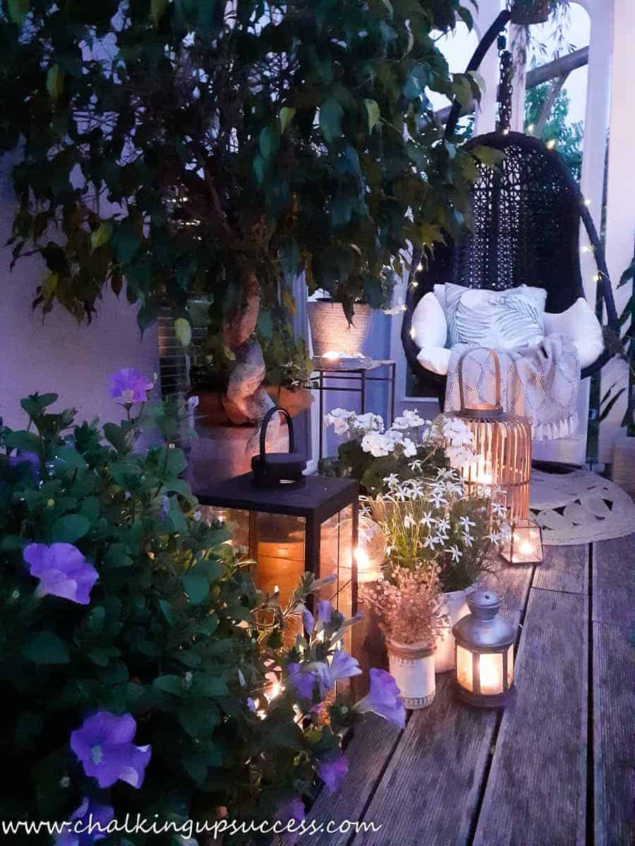 View down the length of a small porch with a black hanging chair at the far end and lots of lit candles and lanterns.