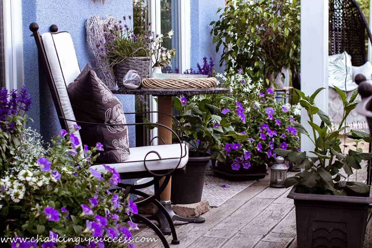 Patio furniture and flower containers on a small porch in summer time.
