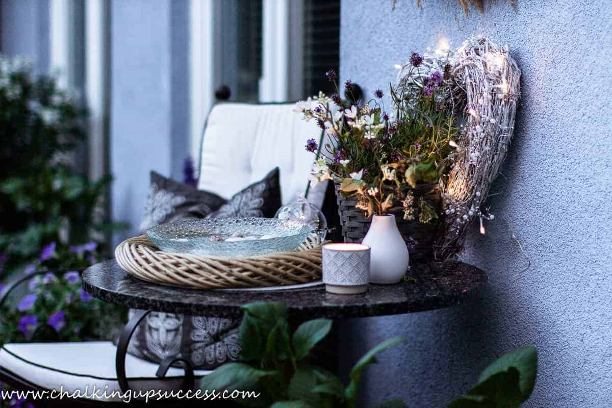 small porch table and chair. The black granite tabletop holds a basket of fresh lavender and an illuminated twig wreath in the shape of a heart.