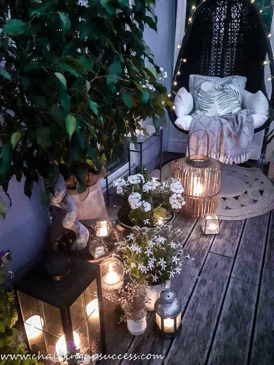 The end of a small porch decorated for summer with white geraniums in containers, and a hanging basket chair decorated with string lights.