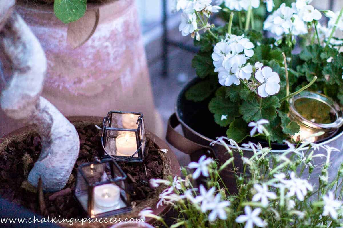 White summer geraniums in pots on a small porch.