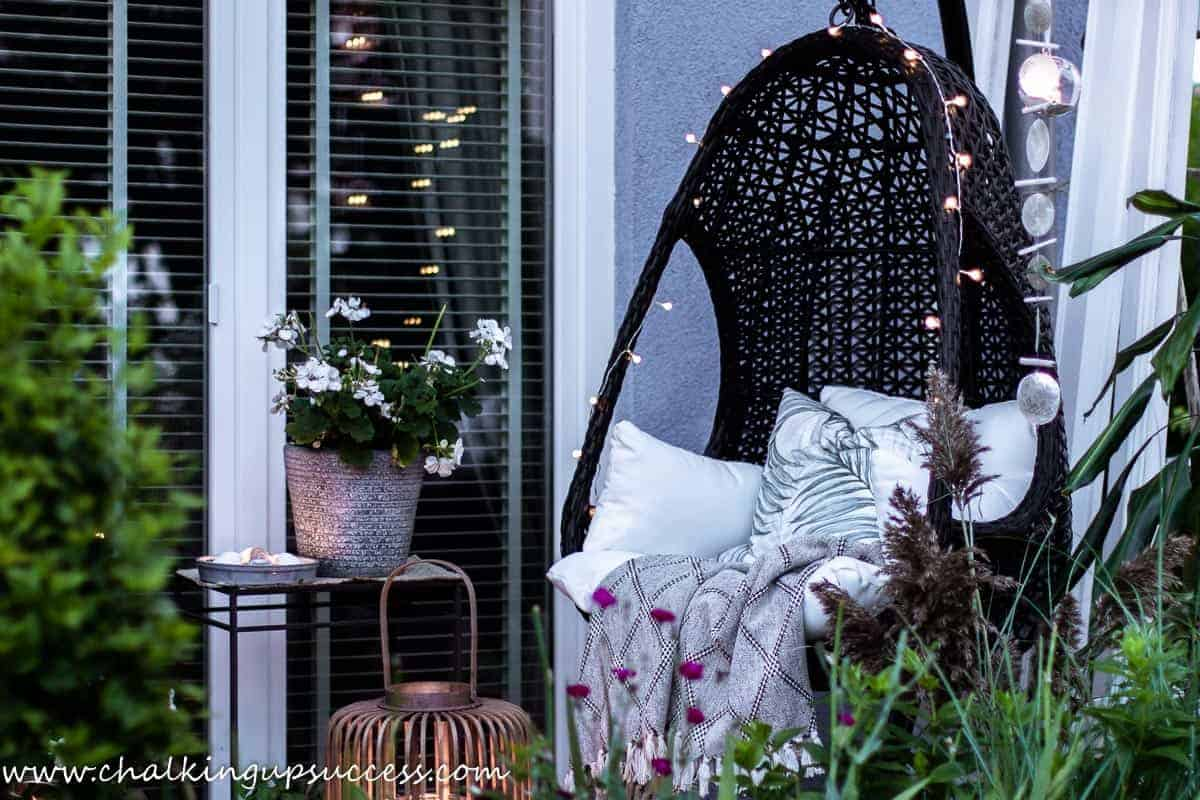 A black basket weave hanging chair decorated with string lights is placed at the end of a small porch.