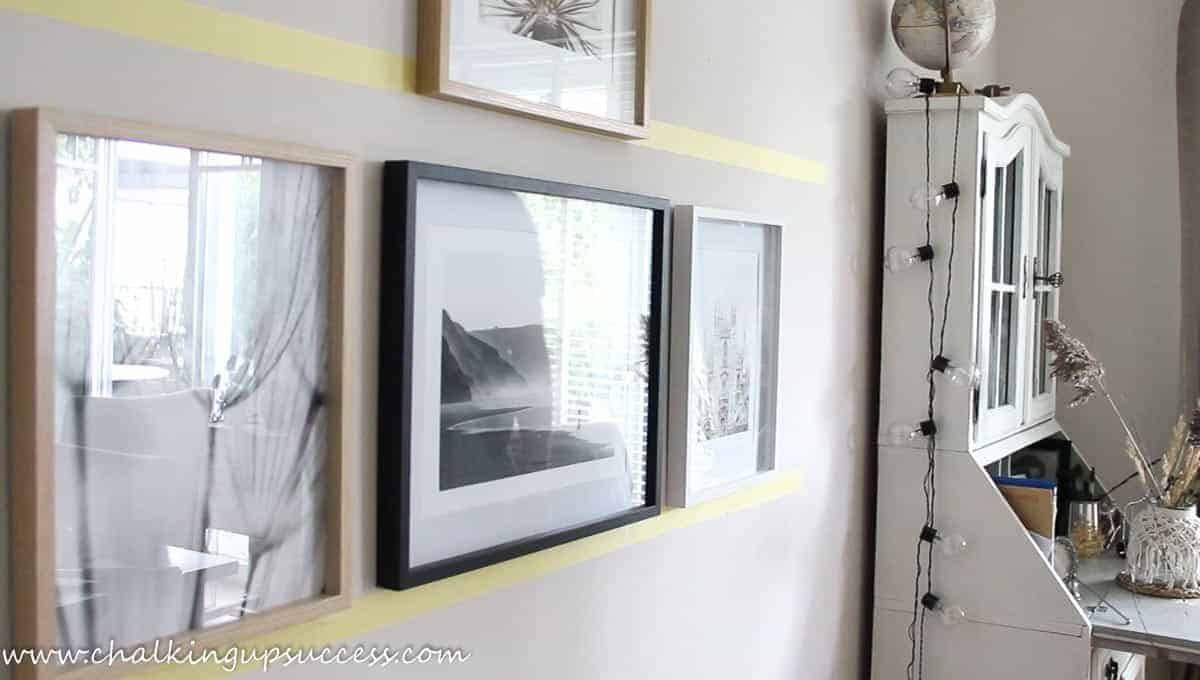 Showing how picture frames have been lined up along yellow painter's tape gallery wall guides..