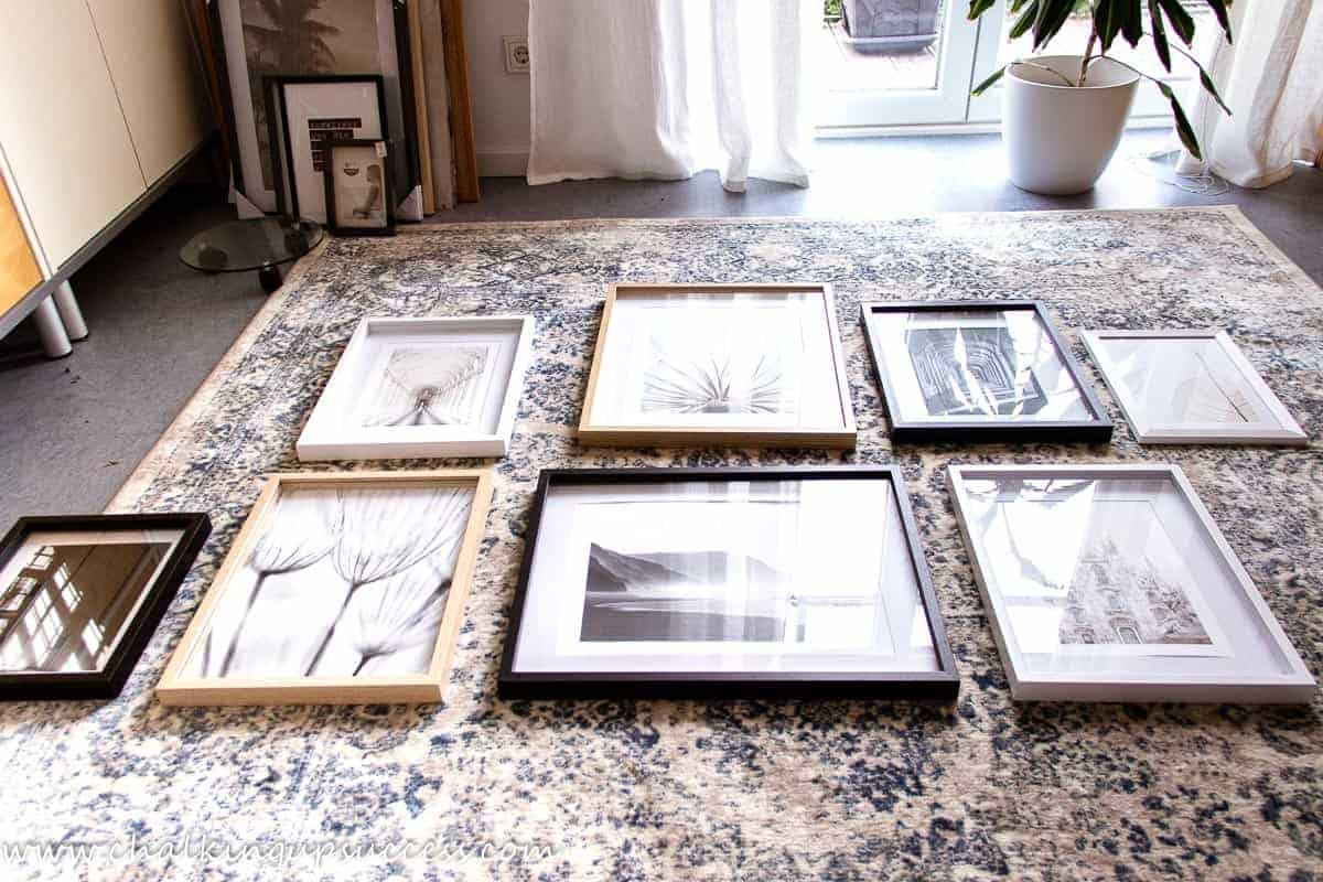 Shows eight pictures in frames, set out on the floor. Finding the correct layout for a gallery wall.