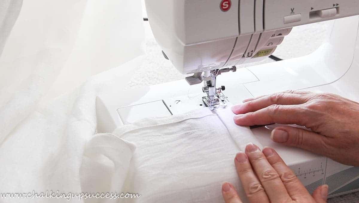 Starting to sew the hem of the curtains at the sewing machine.