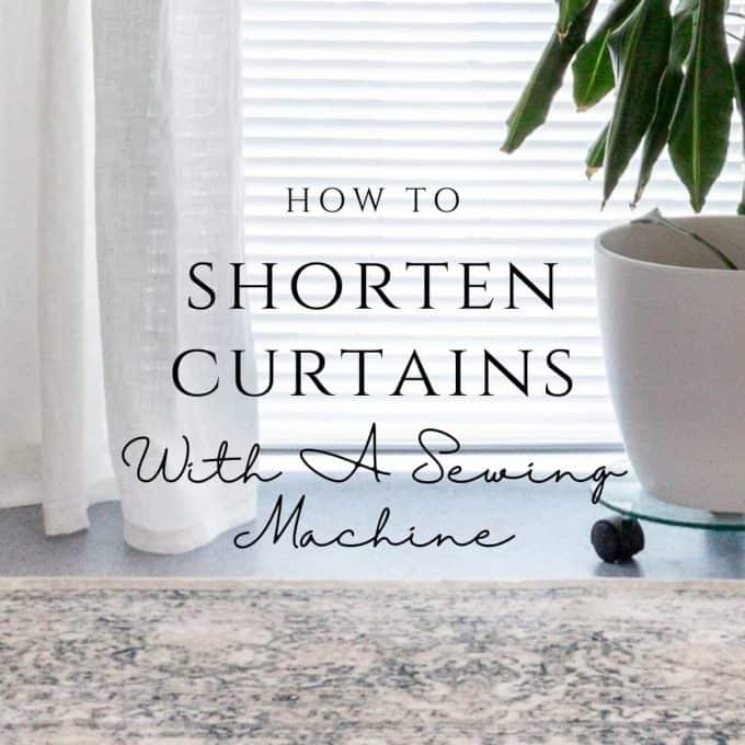 """White linen curtains hanging at a window. A green plant and a white pot stands between the curtains. The text overlay reads, """"How to shorten curtains with a sewing machine"""""""