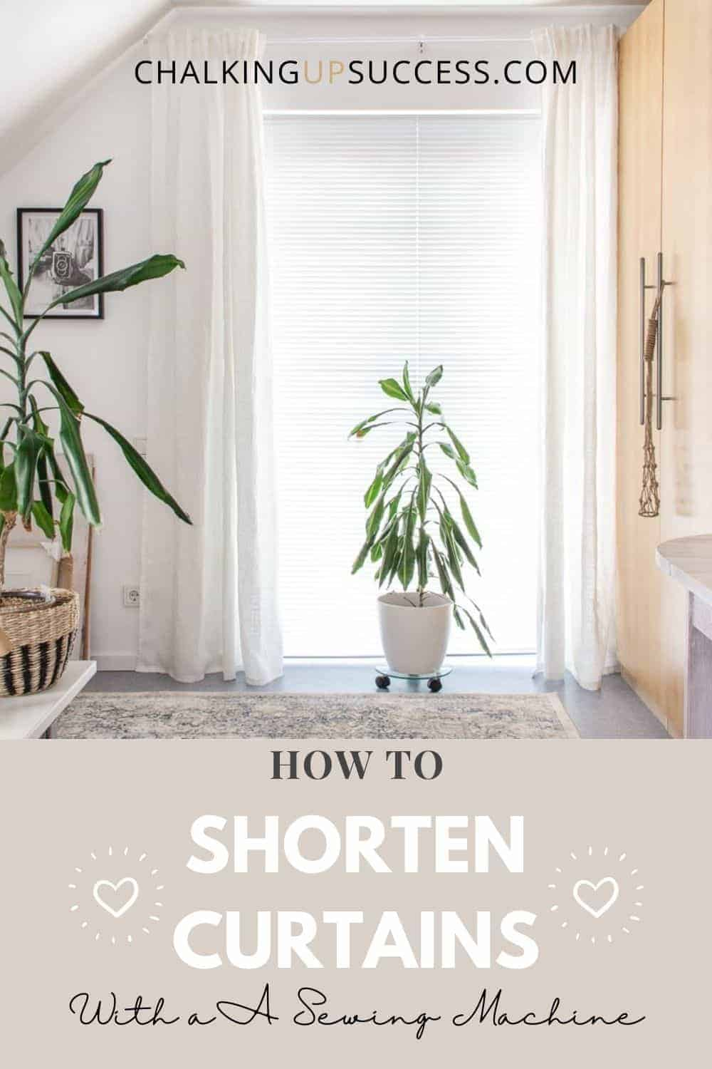 White linen curtains hanging at a window. A green plant and a white pot stands between the curtains.