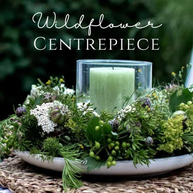 Candle wreath centerpiece. A green pillar candle in a glass hurricane lantern in the middle of a wreath made with wildflowers.