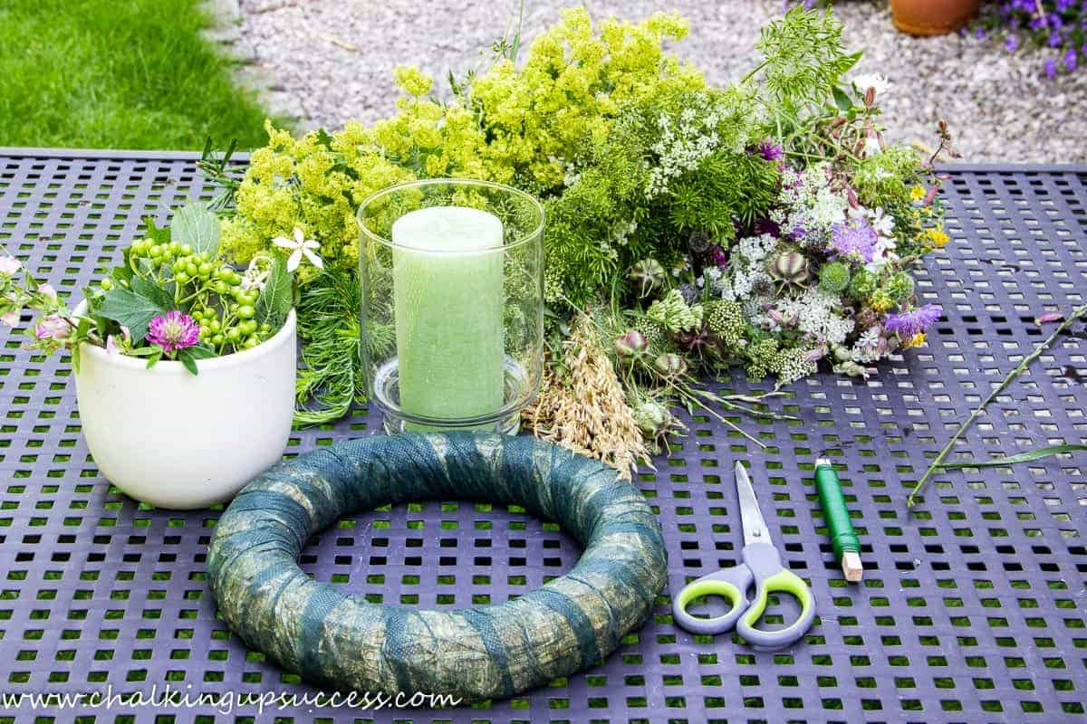 Materials for making a candle wreath centrepiece. A straw wreath, scissors, florist's wire, a glass hurricane lantern, a green pillar candle and a large bunch of wildflowers.