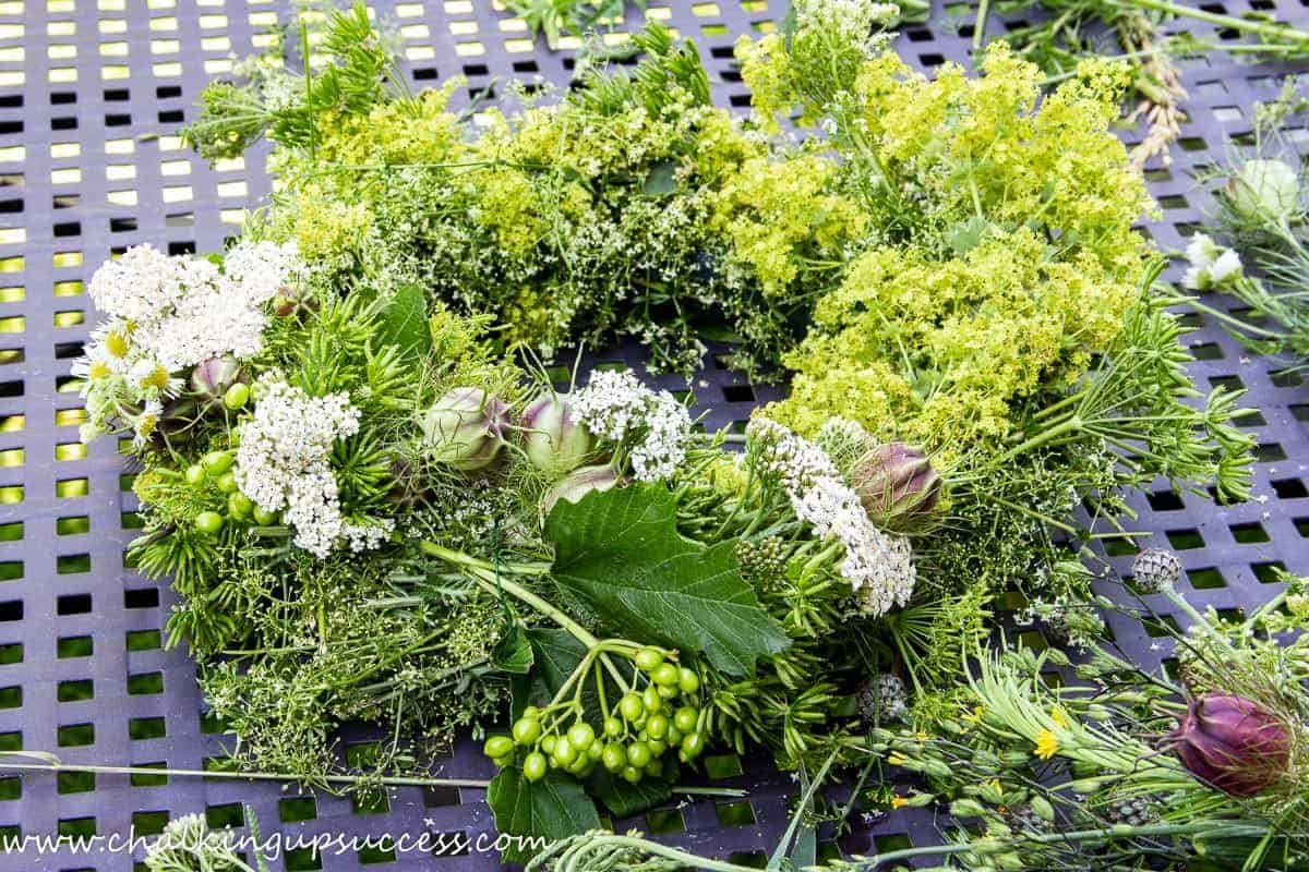 Making a candle wreath centrepiece stage 2 - Adding posies of wildflowers to the base wreath.