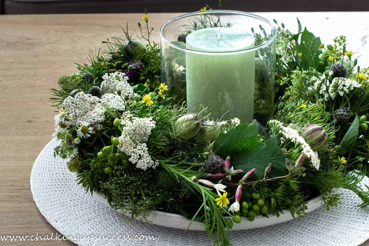 A pretty candle wreath centrepiece. A glass hurricane lantern is placed in the center of the floral wreath-