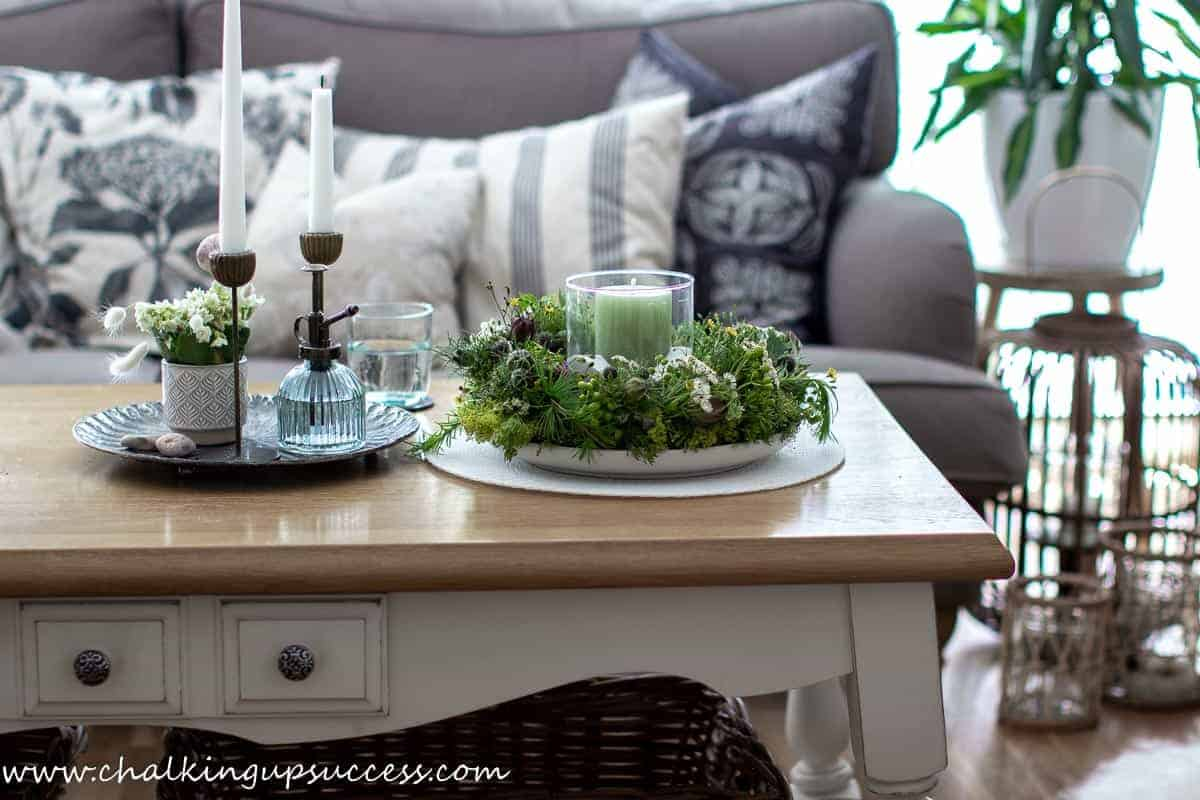 The living room. A coffee table stands in front of a sofa. On the coffee table stands a pretty candle wreath centrepiece and a tray filled with white candles.