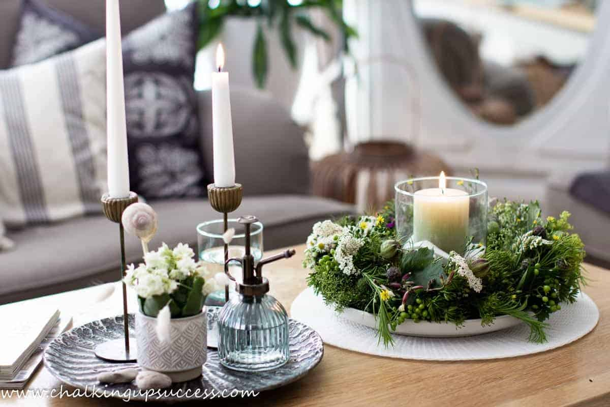 On a coffee table, stands a green pillar candle in a glass hurricane lantern in the middle of a wreath made with wildflowers.