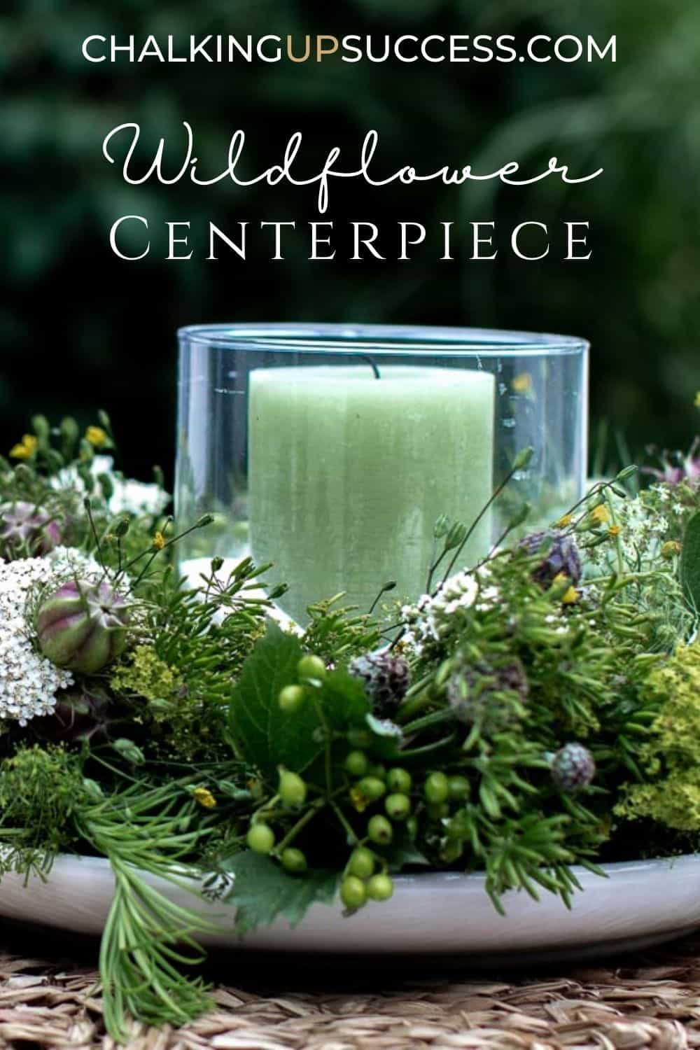 A green pillar candle in a glass hurricane lantern in the middle of a wreath made with wildflowers.