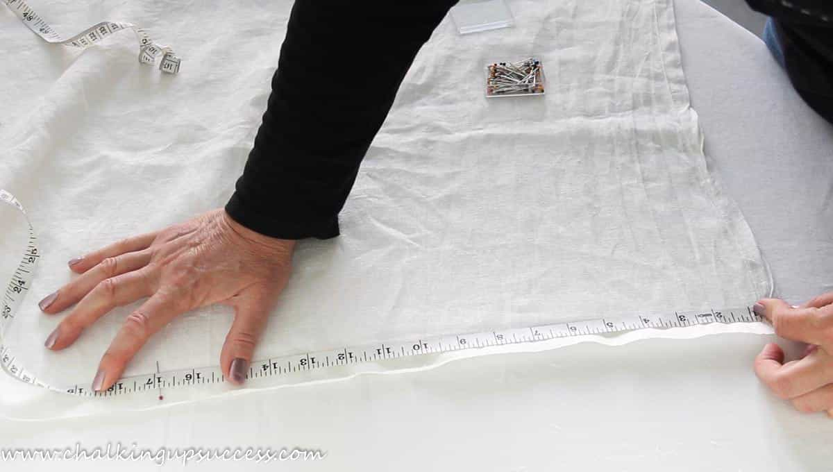 A person measuring a piece of linen material in order to make a napkin.