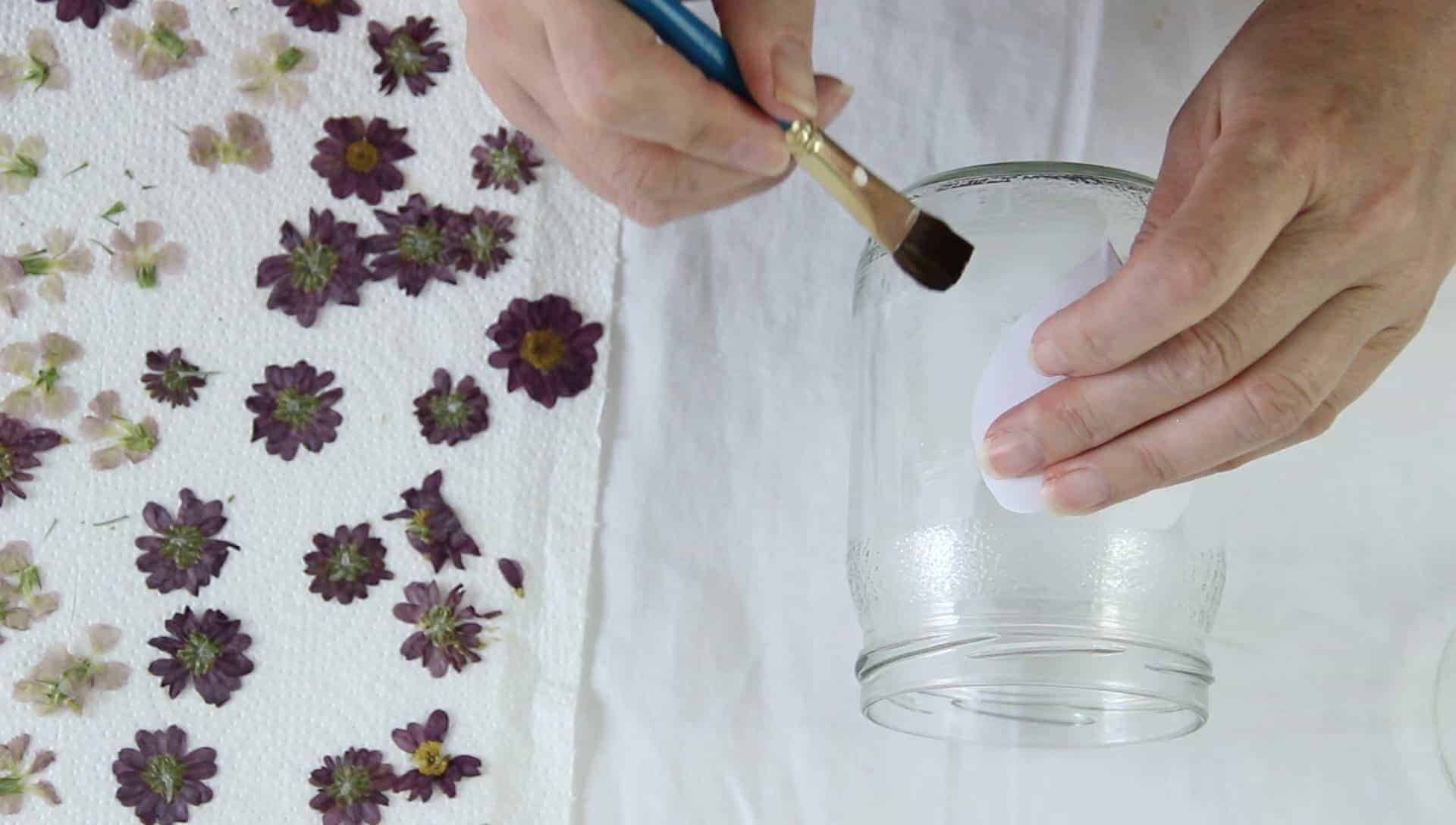 A person's hands using a paintbrush to add glue to a jar to make glass jar lanterns with pressed flowers.