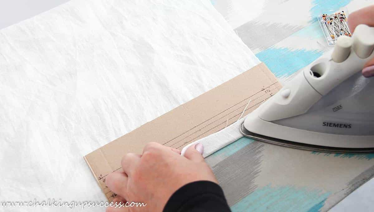 A person ironing a hem ready to make a napkin from fabric.