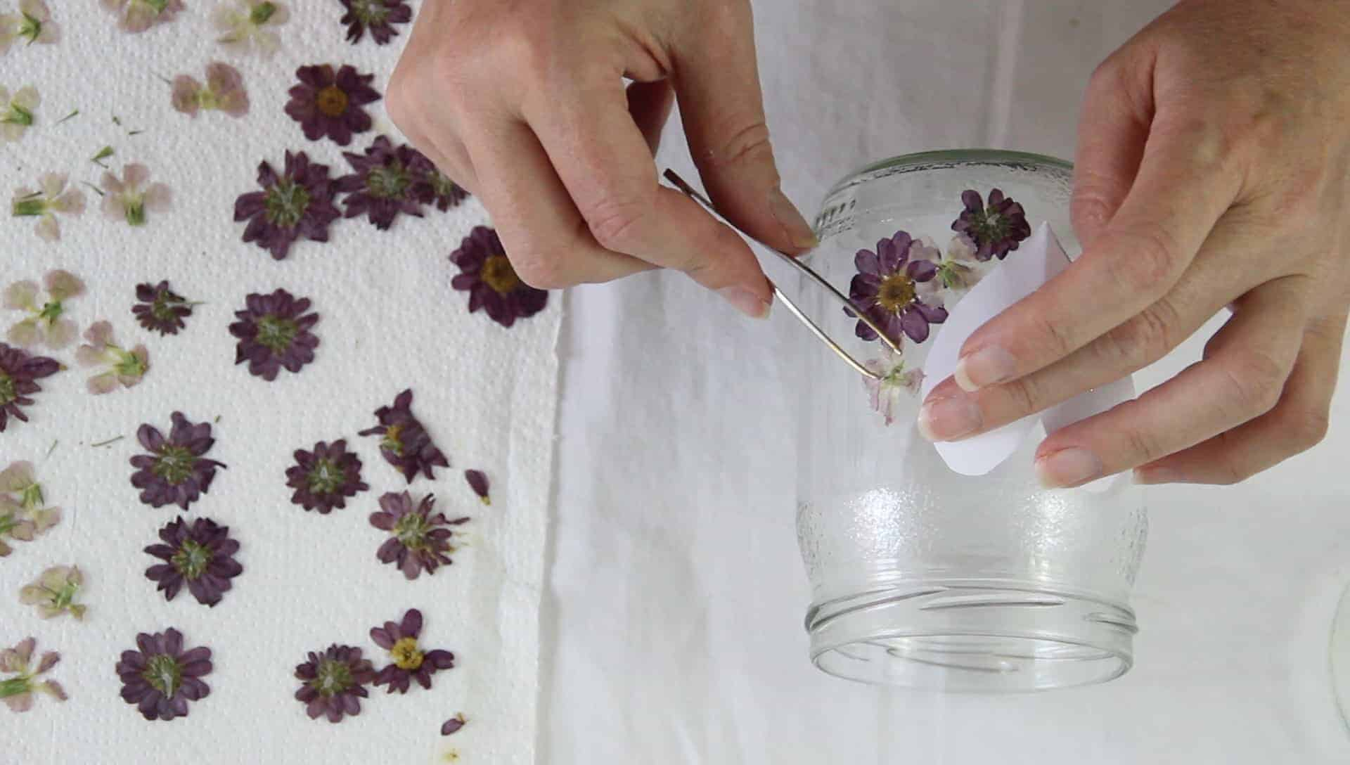 A person's hands showing how to glue pressed flowers onto a glass jar to make glass jar lanterns.
