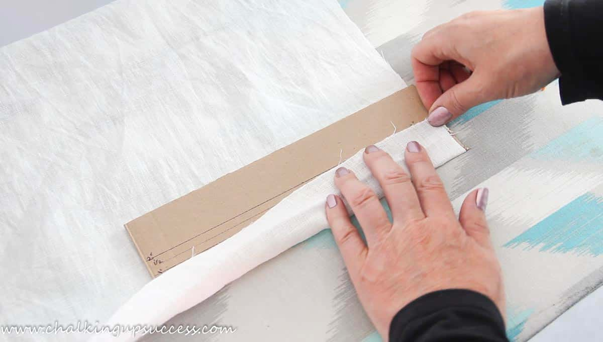 A person folding up a hem ready to make a napkin from fabric.