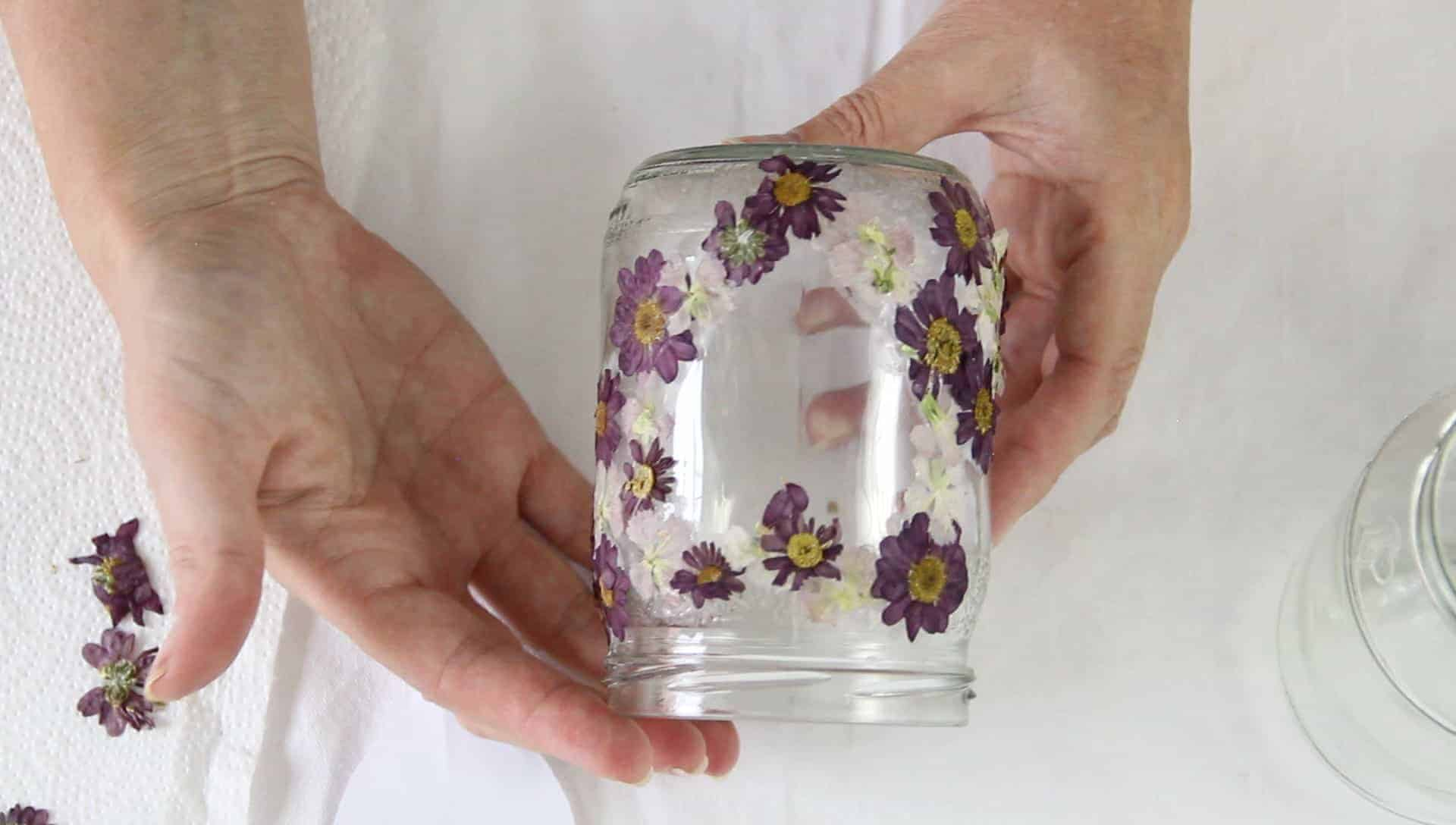 A person's hands showing a glass jar lantern with pressed flowers glued on around a heart shape.
