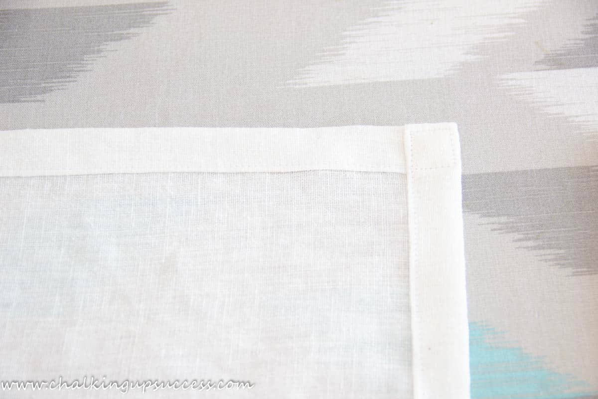The square corner of a white napkin showing how the corner hem has been sewn.