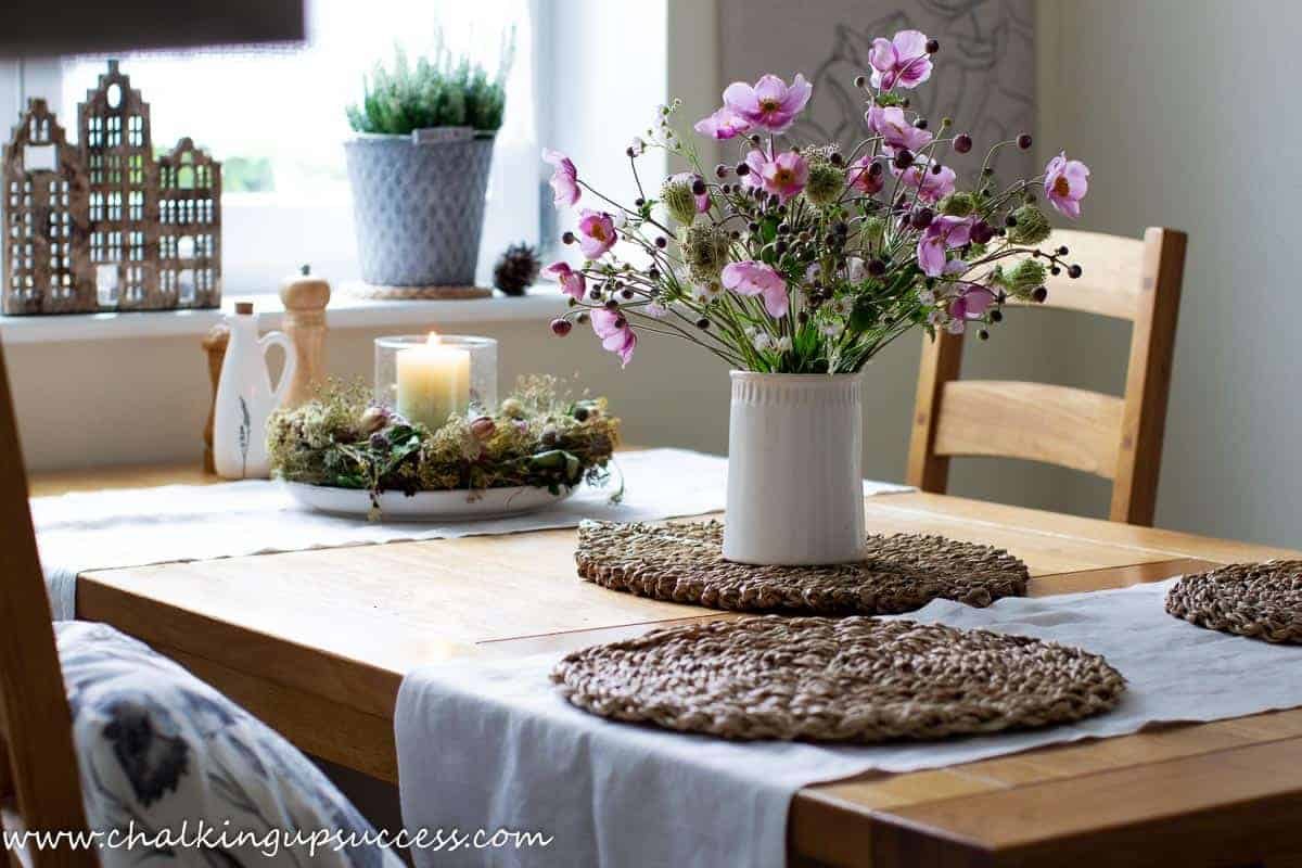 A white ceramic vase filled with Japanese Anemone and wild carrot seedheads standing on a farmhouse table.