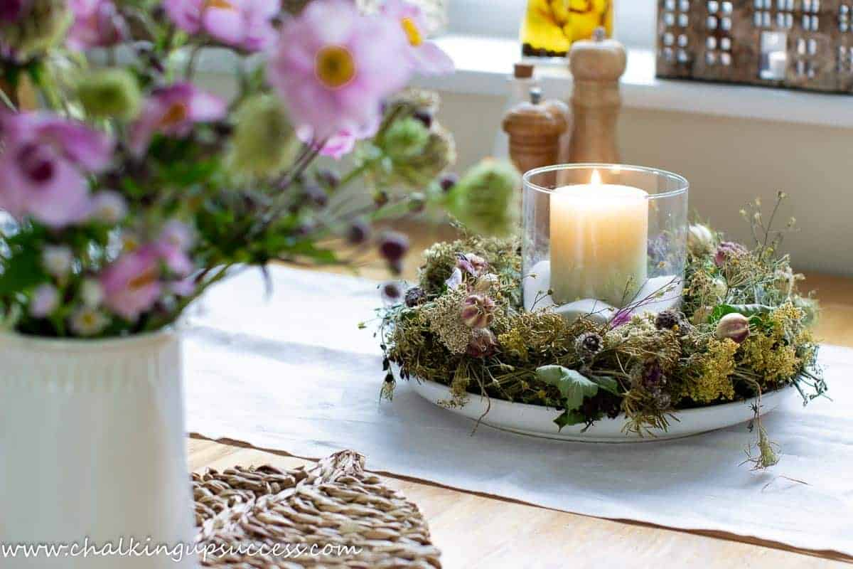 A candle wreath centrepiece made of dried flowers.