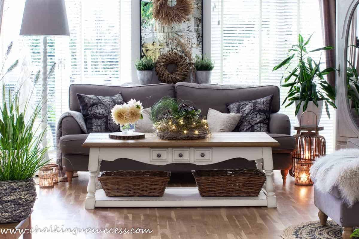 A living room decorated for Fall with lanterns, a vase of Café au lait Dahlias and a coffee table centerpiece of Autumn plants.
