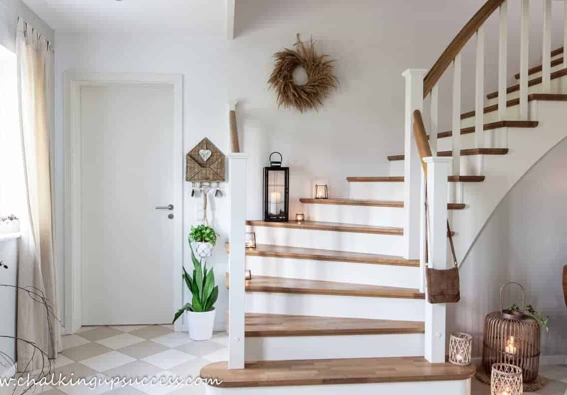 Fall decor ideas in the hallway with lanterns on a wood and white staircase.