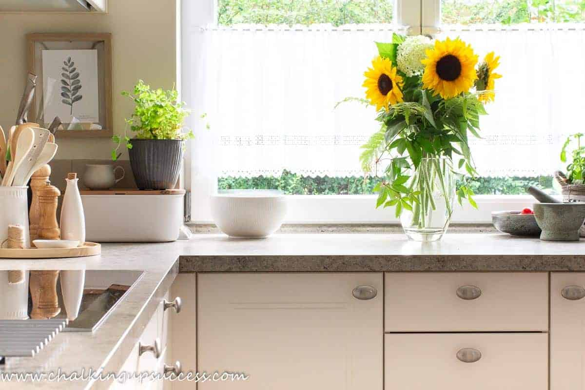 Fall decor ideas for the kitchen - A tall vase filled with happy yellow sunflowers sits on the counter in a corner of a white kitchen.