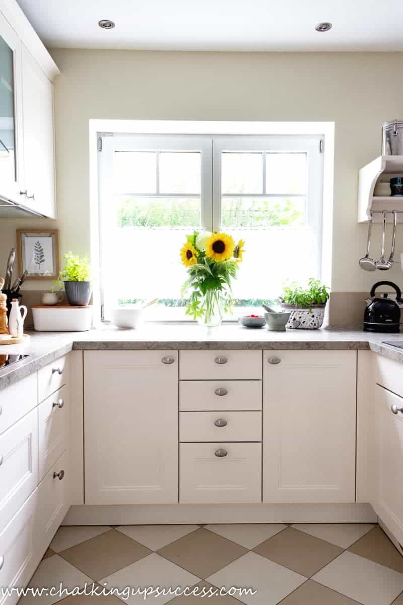 Fall decor ideas for the kitchen - A tall vase filled with happy yellow sunflowers sits on the counter in a white kitchen.