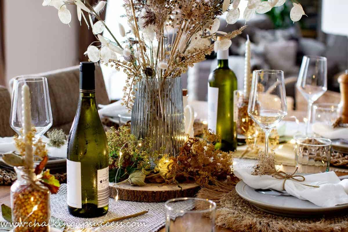 Rustic decor ideas for a Fall tablescape. A vase filled with dried flowers is the centerpiece of the farmhouse table.