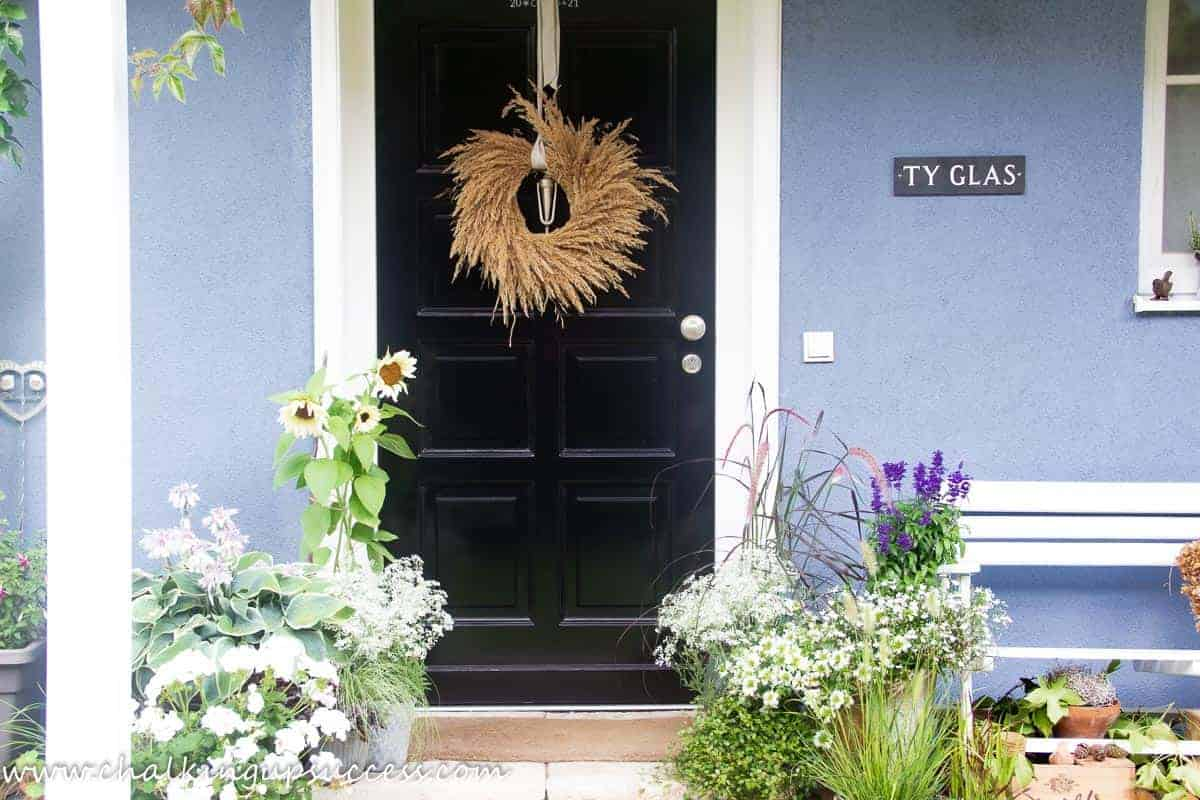 Fall decor ideas for outside - sunflowers, grasses and Hosta in pots outside the front door