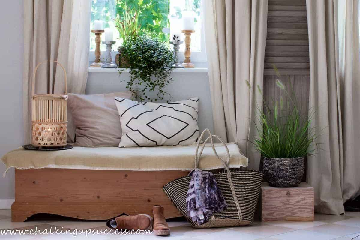 Fall decor ideas - A pretty hallway with a pine bench, comfy pillows and a rattan lantern.