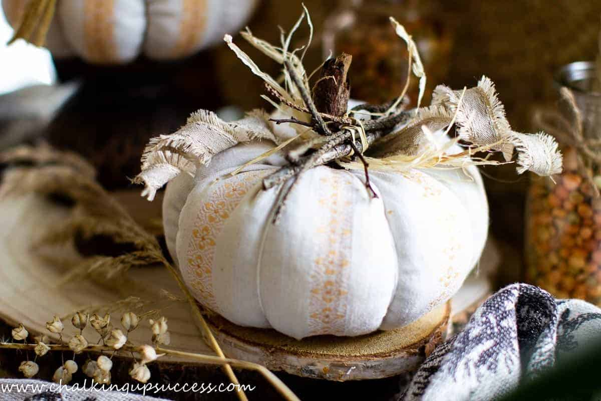 A fabric pumpkin made from pretty orange and cream striped fabric. The top of the fabric pumpkin is decorated with small twigs tied together, some curly ribbon and a raffia bow. The stalk has been made from a small stick.