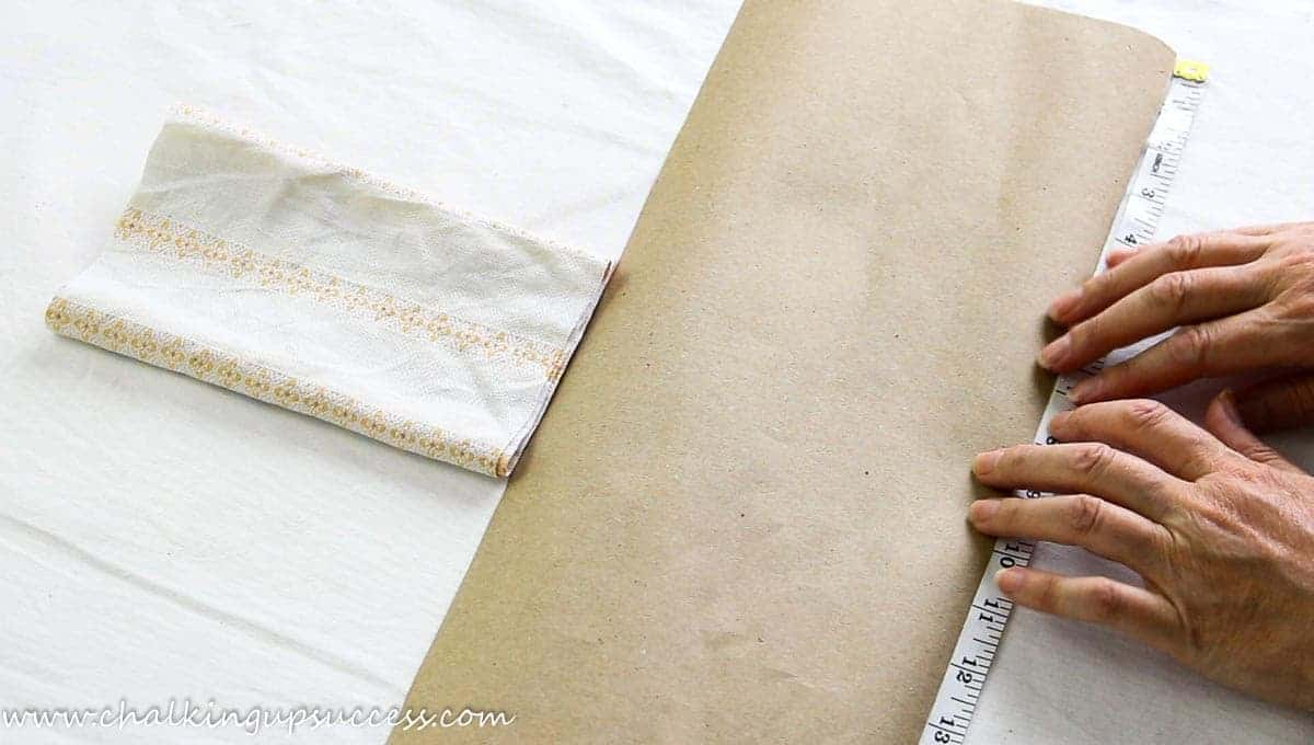 A person showing how to make a fabric pumpkin by cutting out a template from paper.