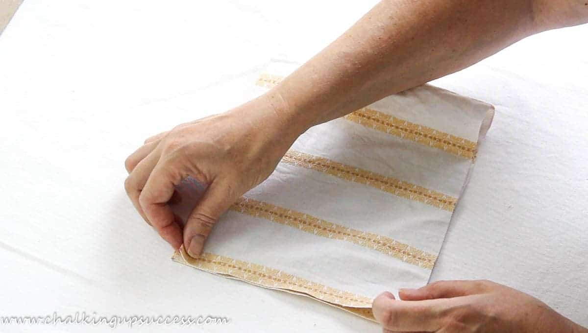 A person showing how to fold over the fabric in order to make a fabric pumpkin