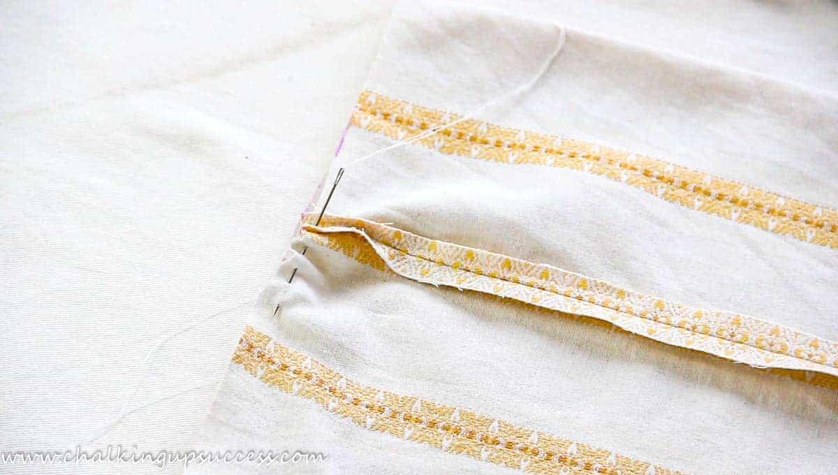 A needle and thread, running through fabric to make a fabric pumpkin