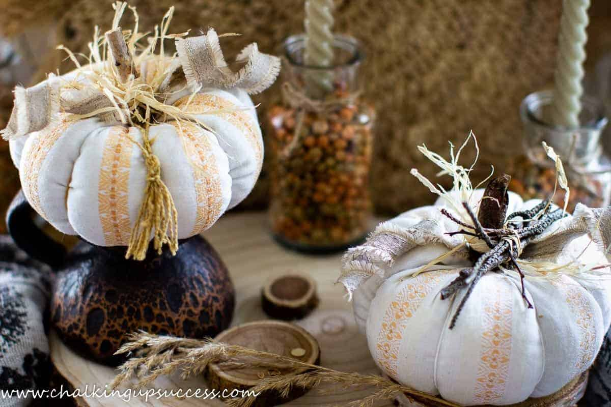 Two fabric pumpkins made from pretty orange and cream striped fabric. The top of the fabric pumpkins is decorated with small twigs tied together, some curly ribbon and a raffia bow. The stalks have been made from small sticks.