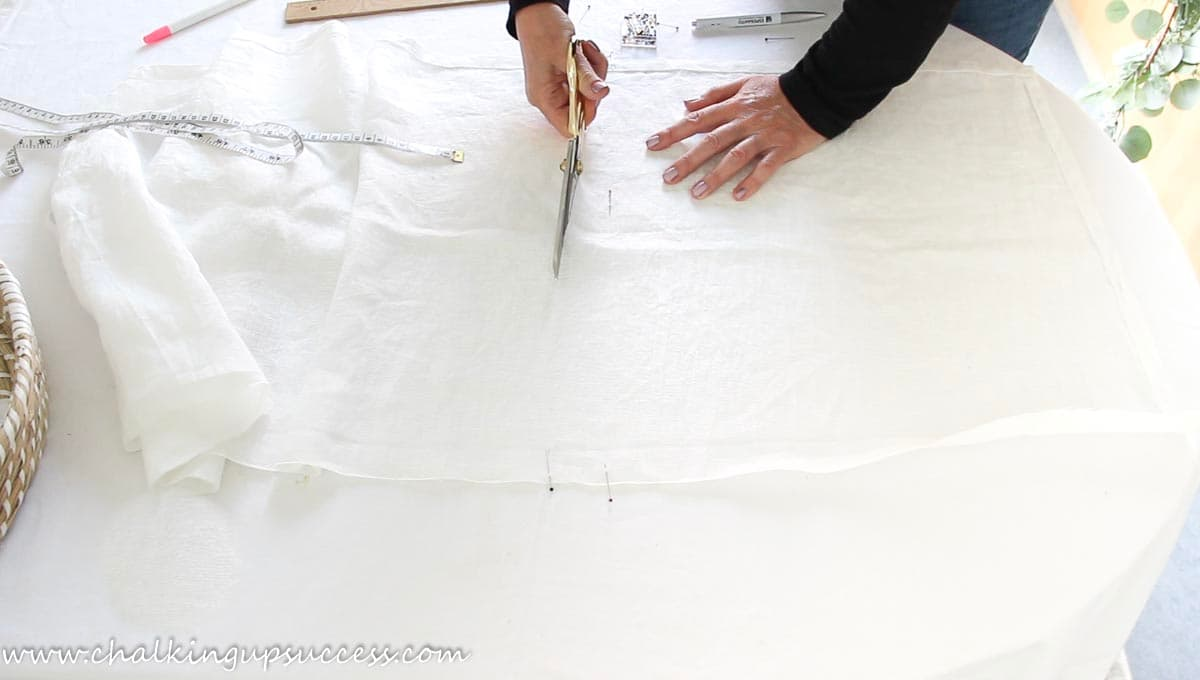 A person cutting fabric with scissors in order to make a napkin from fabric.