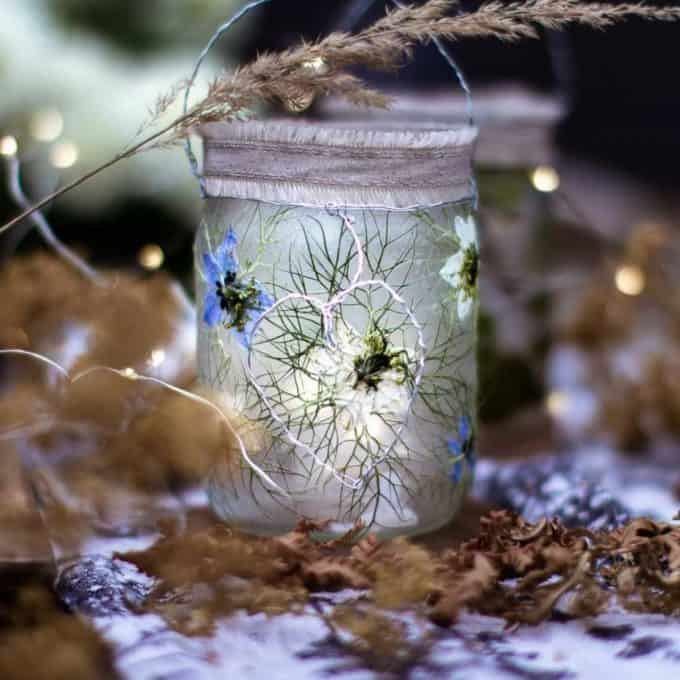 Glass jar lanterns made with pressed flowers in an autumn scene with dried ferns and flowers.