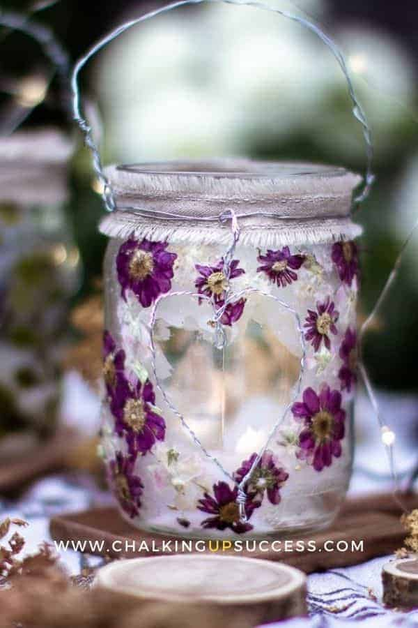 Glass jar lanterns made with small purple pressed flowers.