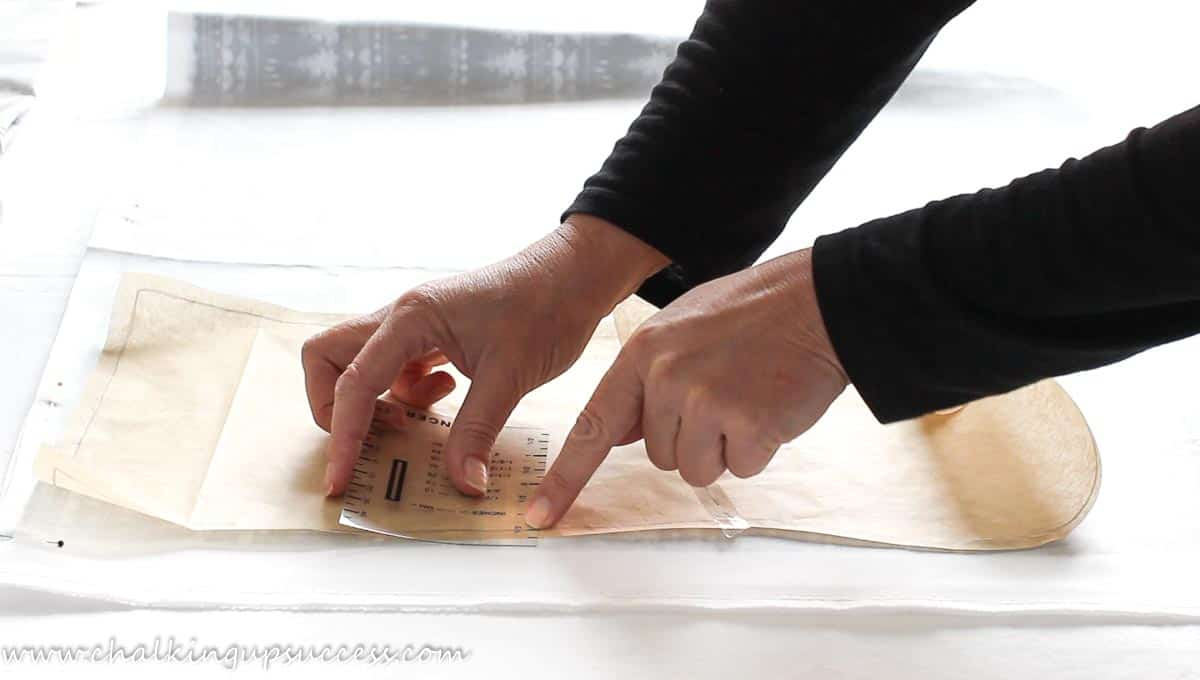A person using a hemming guide to measure the seam allowance for the Christmas stocking.