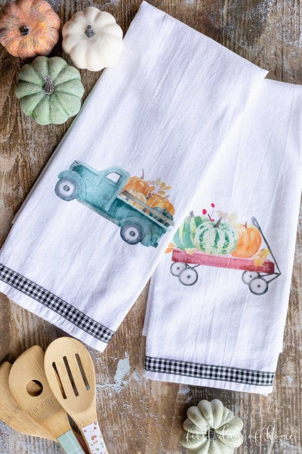 A tea towel with a blue truck and pumpkins and a tea towel with a red wagon filled with pumpkins