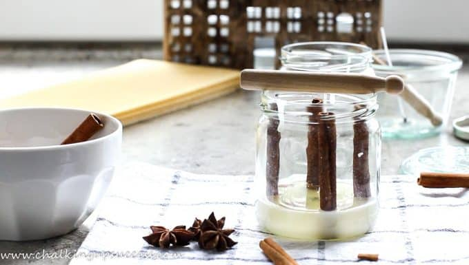 A small amount of soy wax has been poured into the bottom of a glass jar. Four cinnamon sticks have been pushed into the wax at the sides of the jar.
