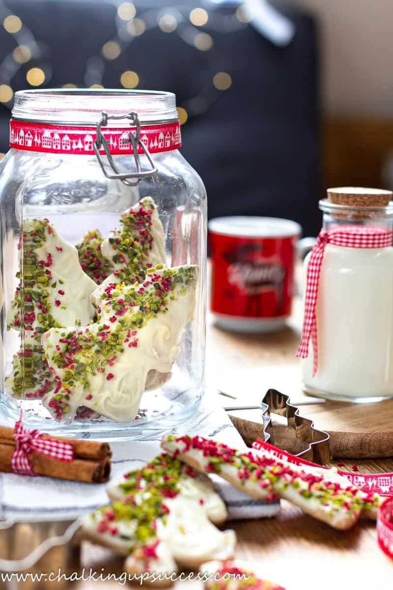 A tall glass jar filled with Chocolate dipped Christmas tree cookies.