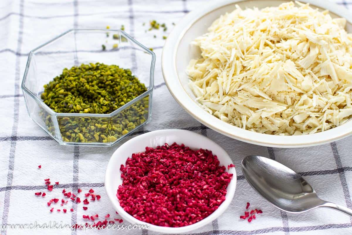 Ingredients for decorating chocolate dipped Christmas tree cookies - white chocolate, pistachios and freeze-dried raspberries..